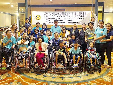車椅子の寄贈の後、参加者全員で記念撮影(提供)